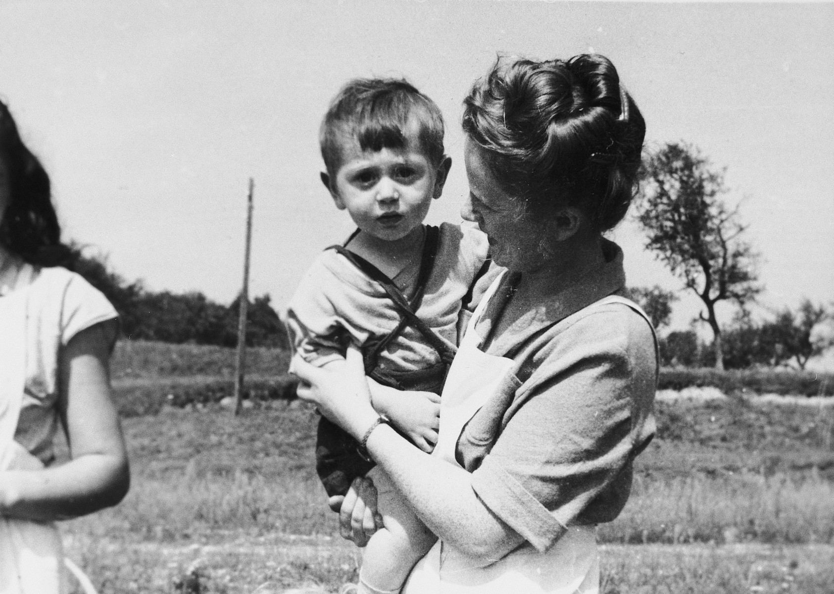 A woman poses holding a child in a field at a Jewish displaced persons camp in Austria (probably Bindermichl).