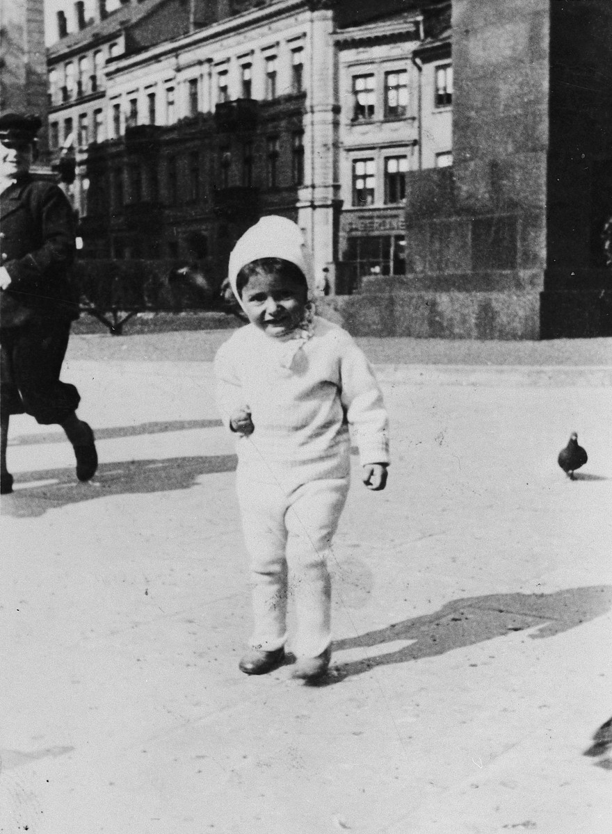 """A young Jewish child chases pigeons on a street in Warsaw.  Pictured is Yosele Federman.  The inscription on the back reads, """"As a memory for my dear aunt, uncle and cousin.  Yosele Federman""""."""