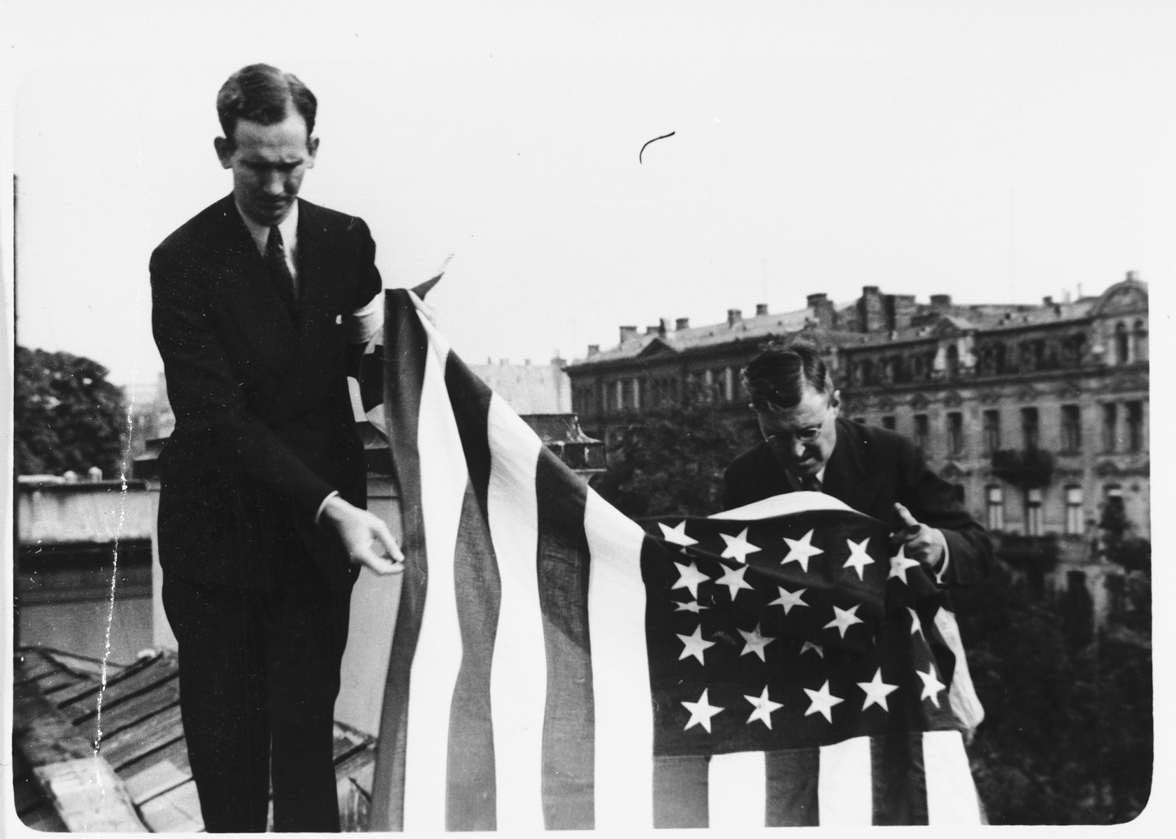 """Two American consular staff members hang an American flag from the roof of the embassy in Warsaw in anticipation of the arrival of German troops into the capital.    Photographer Julien Bryan describes the scene:  """"On September 12 [1939] word came over the radio that the German army was entering the city.  Out came all the available American flags.  The largest - ten by fifteen feet - was carried to the roof.  The other flags we suspended in front of the embassy and also at the rear, believing the German troops might approach from that direction.  Finally we placed one small flag over the dugout in the garden.  But the Germans did not come that day, nor did they come while we were in Warsaw."""" [Source: Bryan, Julien.  """"Warsaw 1939 Siege; 1959 Warsaw Revisited.  Warsaw, Polonia, 1959, p. 31.]"""