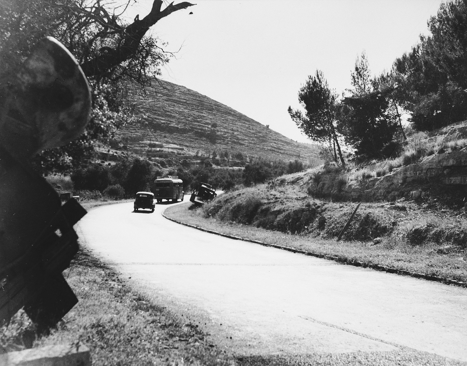 A car and a bus drive past an abandoned military vehicle on the road to Jerusalem.