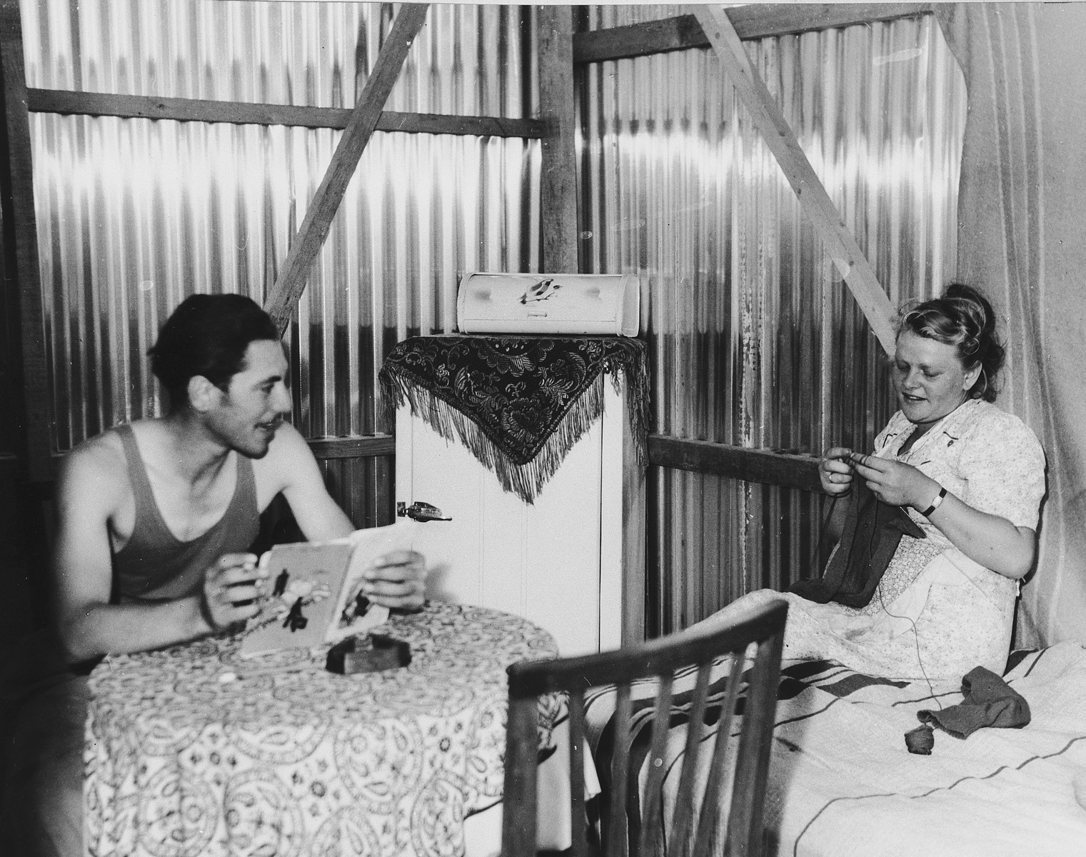 A young couple sits in their hut in Tel Shachar and reads and knits.