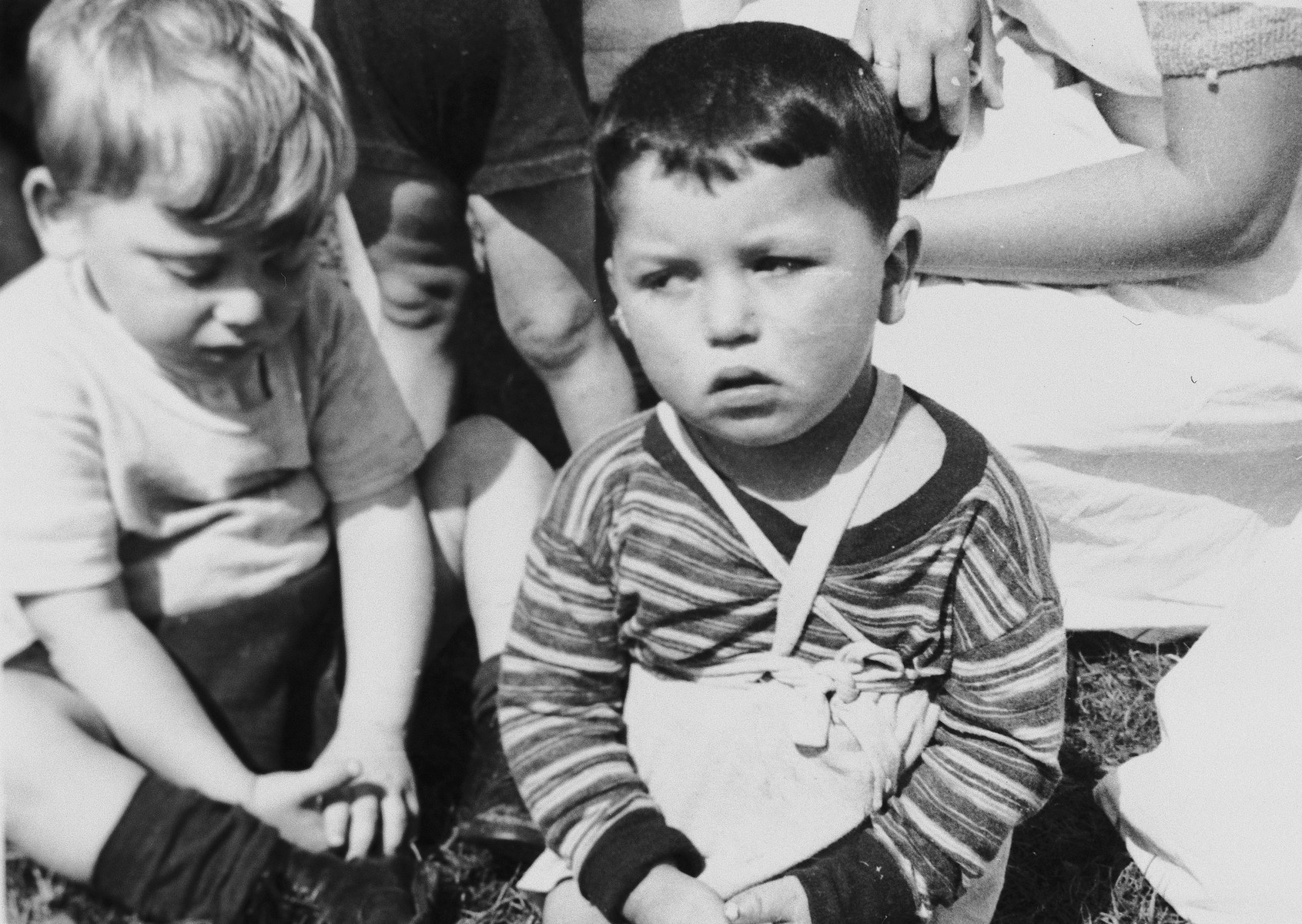 Pre-school age DP children sit outside in a field in a Jewish displaced persons camp in Austria (probably Bindermichl).