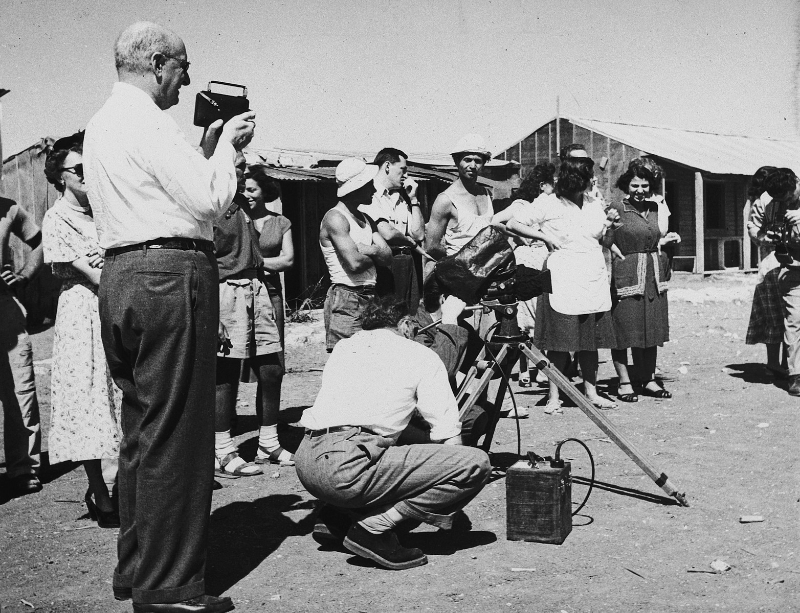 """Henry Morgenthau Jr. takes photographs of new immigrants in Tel Shachar while Robert Capa films the same scene for his 1951 documentary, """"The Journey"""".    The film was shot at the behest of the United Jewish Appeal.  Henry Morgenthau served as honorary chairman of the Appeal."""