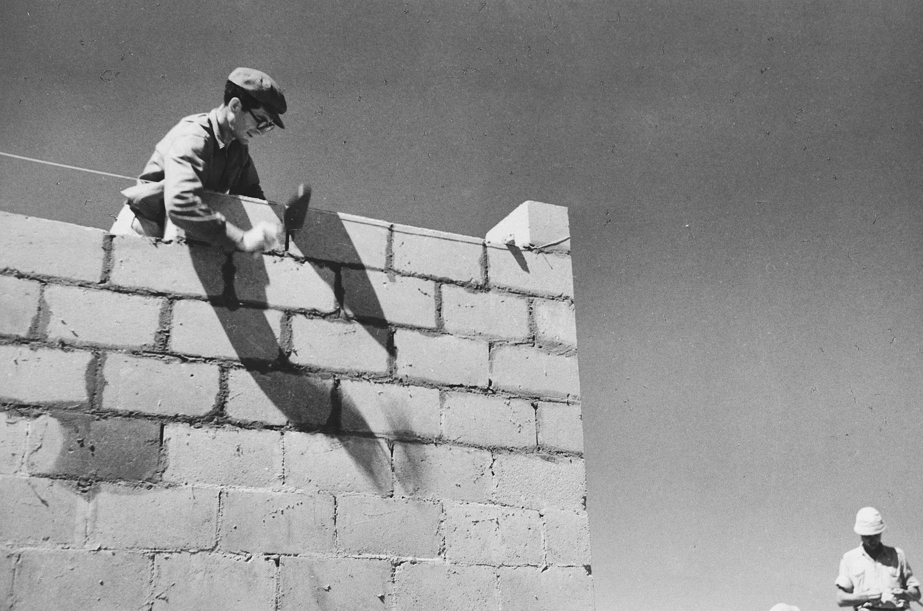 A man constructs a brick wall in Tel Shachar.