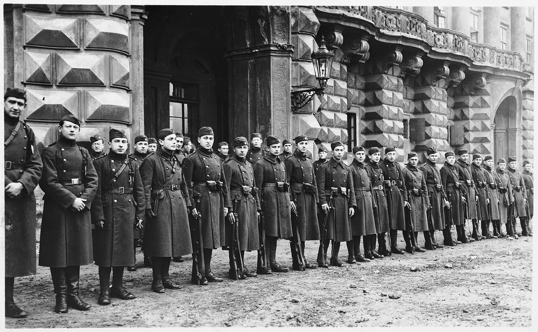 Czech soldiers stand at attention in front of  the Czernin Palace.  Ota Margolius is pictured fourth from the left.
