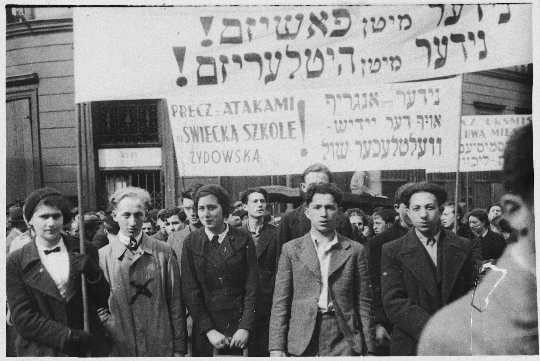 """Warsaw Jews demonstrate against Hitlerism, Fascism and attacks on Jewish schools.  The signs read """"Down with Fascism; Down with Hitlerism"""" and """"We denounce attacks on Jewish schools.""""   The Polish banner reads, """"Down with attacks on secular Jewish schools"""".  Yankel Federman is pictured second from the left.  The caption on the back of the photo reads, """"This card shows a demonstration that took place in Warsaw in 1937 against Fascism and Hitlerism.  I am standing under the banner about the struggle with Hitlerism and the Polish regime in its attacks on Jewish schools and the Yiddish language."""""""