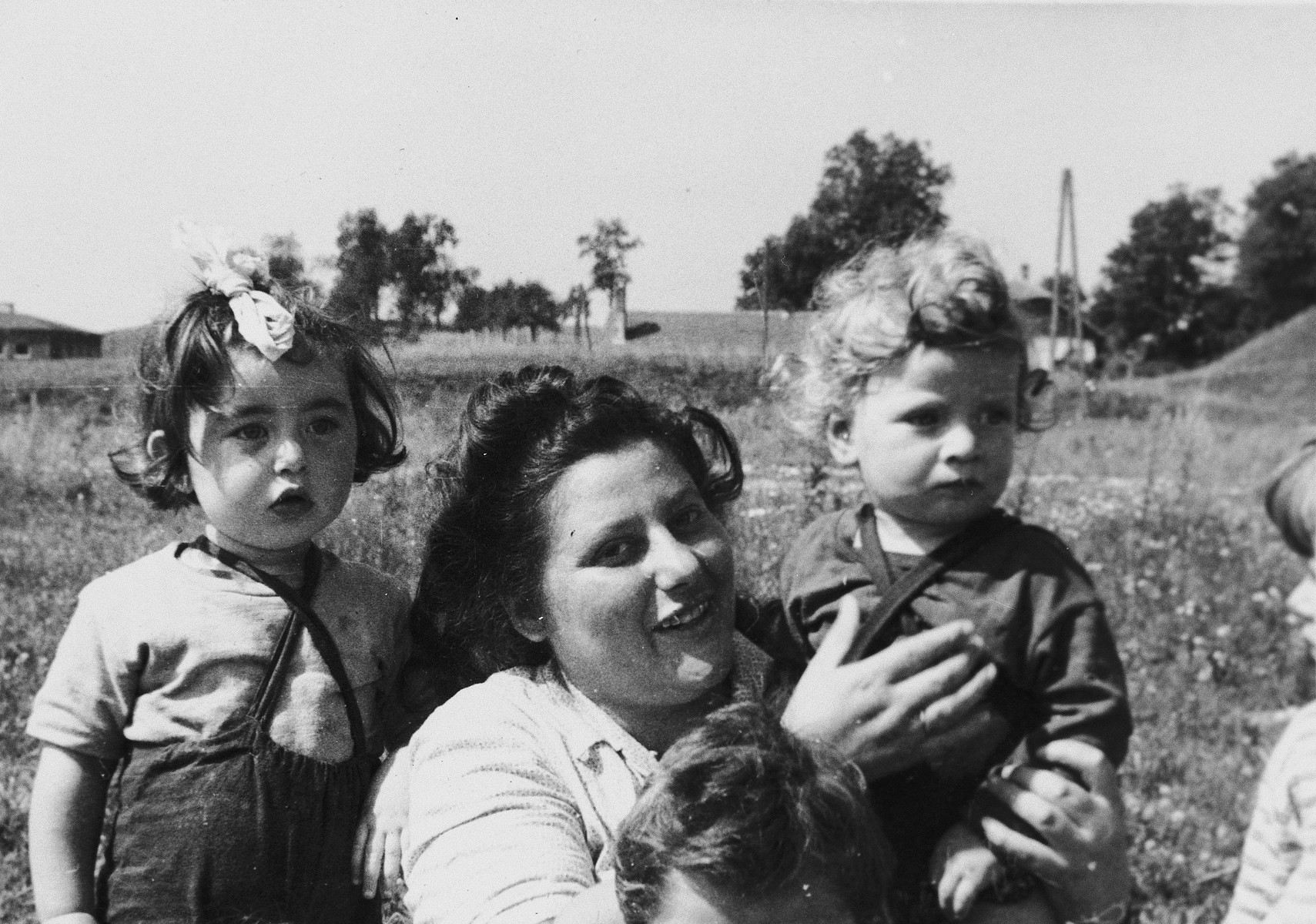 A woman poses with pre-school age children outside in a field at a Jewish displaced persons camp in Austria (probably Bindermichl).