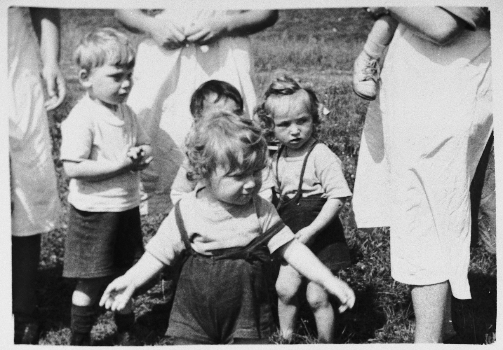 A group of pre-school age children stand in a field at a Jewish displaced persons camp in Austria (probably Bindermichl).
