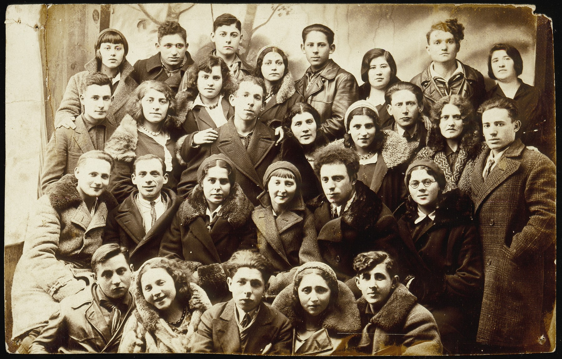 Group portrait of members of the Zionist youth movement, Hashomer Hatzair, from Eisiskes and surrounding towns.      Among those pictured are: back row, right to left: Hinde Gutlevski, visitor, Reshke Gutlevski, visitor, Kreinke Bichwid, Muni Zahavi, Bichwid (sister of Kreinke); second row from the top, right to left:  Motke Burstein, Flora Kagan, Shmuel Berkowicz, unknown, Matikanski, unknown, Bichwid (first name unknown), Rina Lewinson, Hanan Polaczek; third row from the top, right to left: Etele Lubetski, visitor, Esther Katz Resnik, Miriam Koppelman Ruskin, Hayyim Streletski, unknown; front row, right to left: visitor from Olkeniki, Bavale Polaczek, visitor, Leipke Politacki, visitor.    Muni Zahavi, Rina Lewinson, Shmuel Berkowicz, and Bavale Polaczek immigrated to Palestine.  All the others were murdered during the Holocaust.