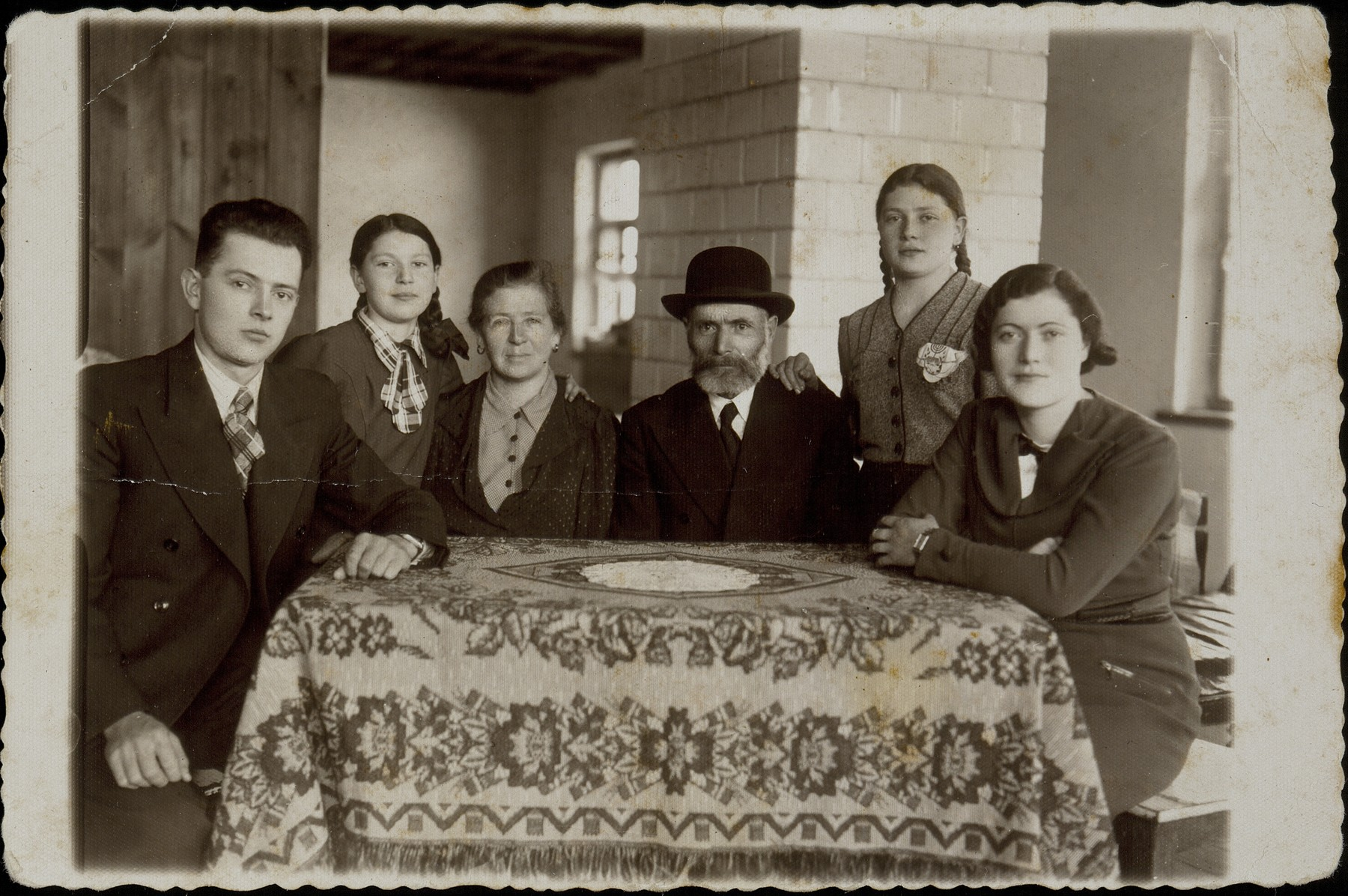 The Dubczanski family celebrates the third night of Hannukah together in their newly rebuilt house.   (right to left) Hannah, Rivka, father Hayyim-Moshe, mother Sarah, Masha, and Shlomo.  All were murdered by the Germans during the September 1941 mass killing action in Eisiskes.