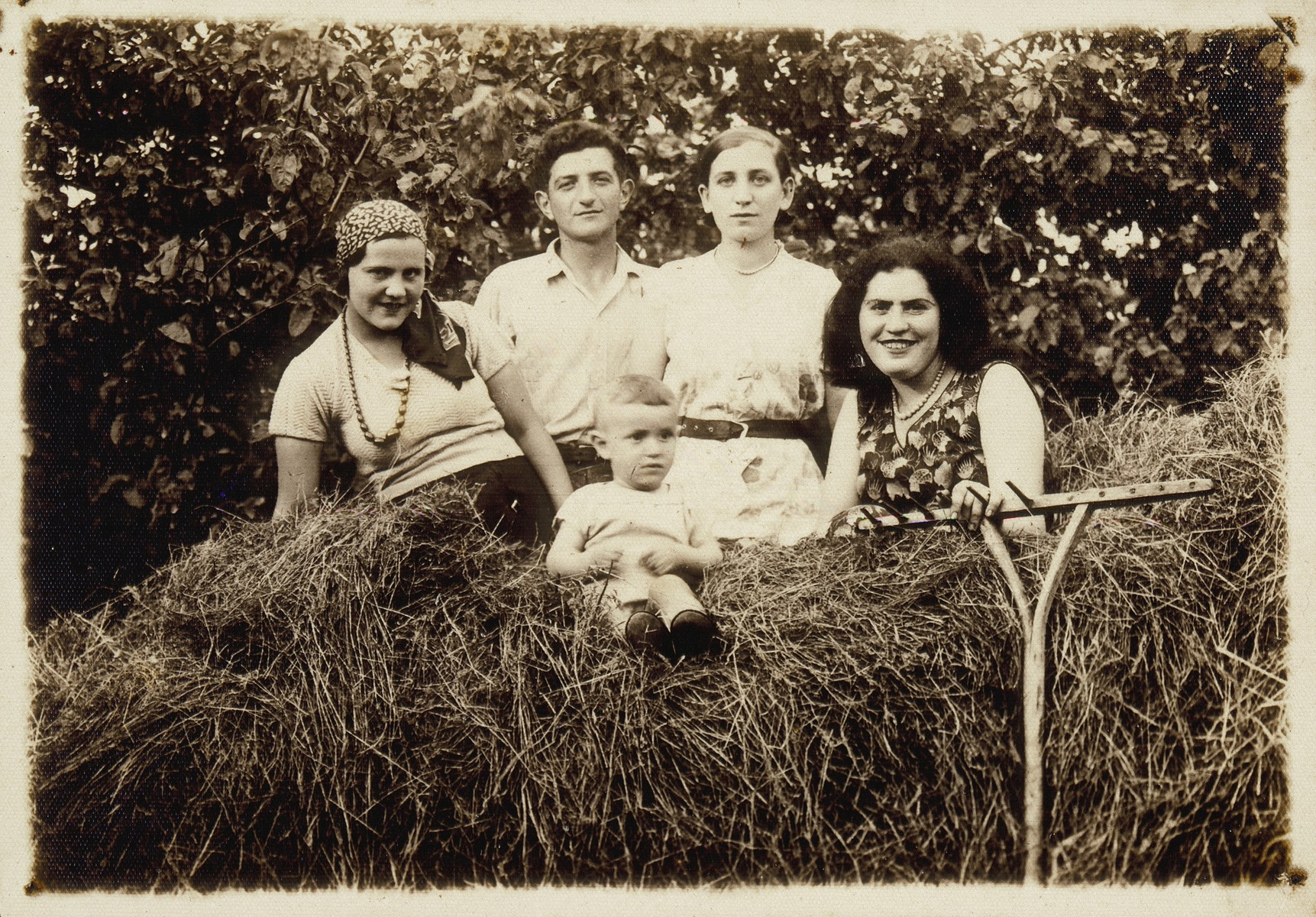 Four young people and a young baby sit on top of a hay wagon.   (right to left) Miriam Koppelman Rushkin, an unidentified visitor, Shepske Sonenson, Malka Nochomowicz, and baby Elisha Rushkin.  Miriam died a natural death; all the others were killed by the Germans during the September 1941 mass shooting action in Eisiskes.