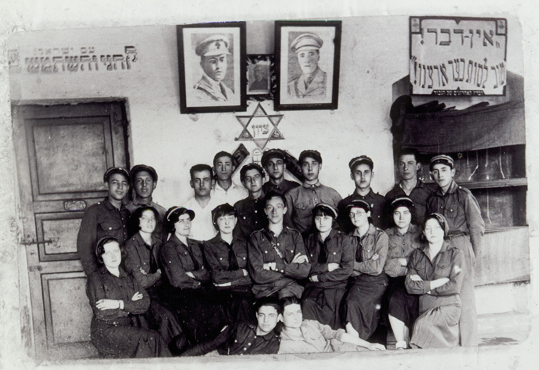 A meeting of Betar leaders and counselors in Eisiskes.    On the wall the photo on the right is of Joseph Trumpeldor, and the photo on the left is of  Vladimir Jabotinsky. Top row: third from right: Zvi Hirshke Schwartz and sixth from right: Shepske (Shabtai) Sonenson  Seated second from right is Rachel Lewinson, third from right is Shoshana Hutner Hinski, sixth from the right is Shoshana Katz and on the far left is Miriam Kabacznik.     Rachel Lewinson and Shoshana Hutner Hinski immigrated to Palestine. Miriam  Kabacznik survived the Holocaust in hiding.  Shepshke (Shabtai) Sonenson, Zvi Hishke Schwartz and Shoshana Katz were murdered in the September 1941 massacre.