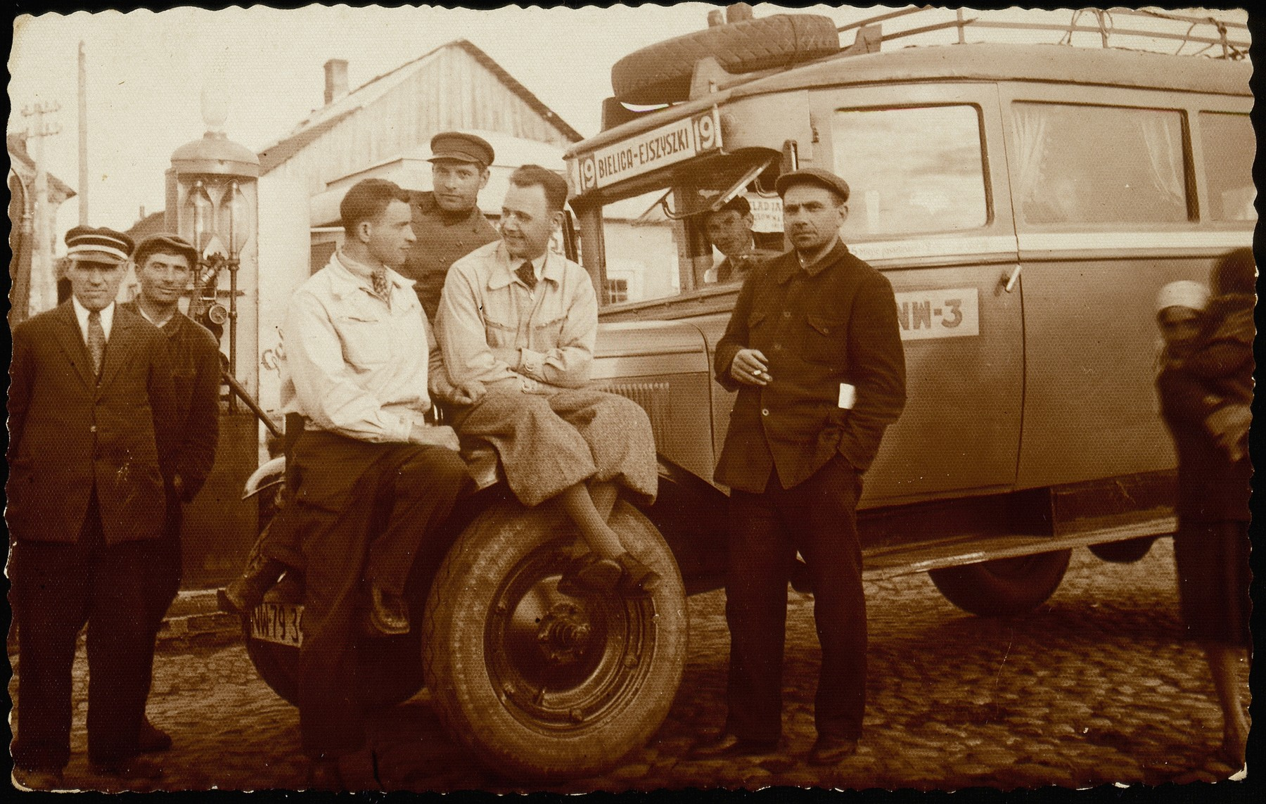 A group of men gather by the Bielica-Ejszyszki bus to Lida at the shtetl bus-stop and gasoline pump.   (Right  to left)  Moshe Slonimski, in the driver's seat is Israel Erlich, between the two Polish drivers is Yankele Krisilov, the shtetl bus driver, Avraham Asner (uncle of Ed Asner), in front of the gasoline pump and Yankele Krisilov, who survived in Russia.  The others were murdered by the Germans and the AK.