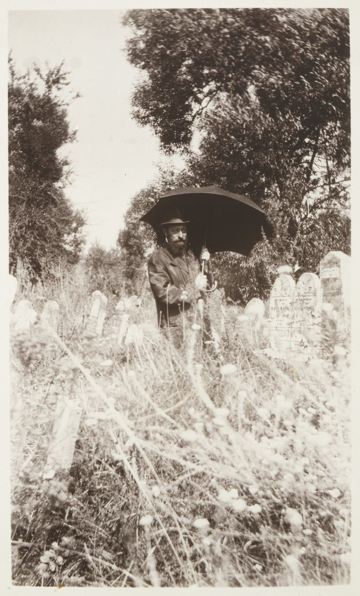 Rabbi Hertz Mendl (Naftali Menachem) Hutner, carrying an umbrella, guides visitors through the Eisiskes' cemetery.