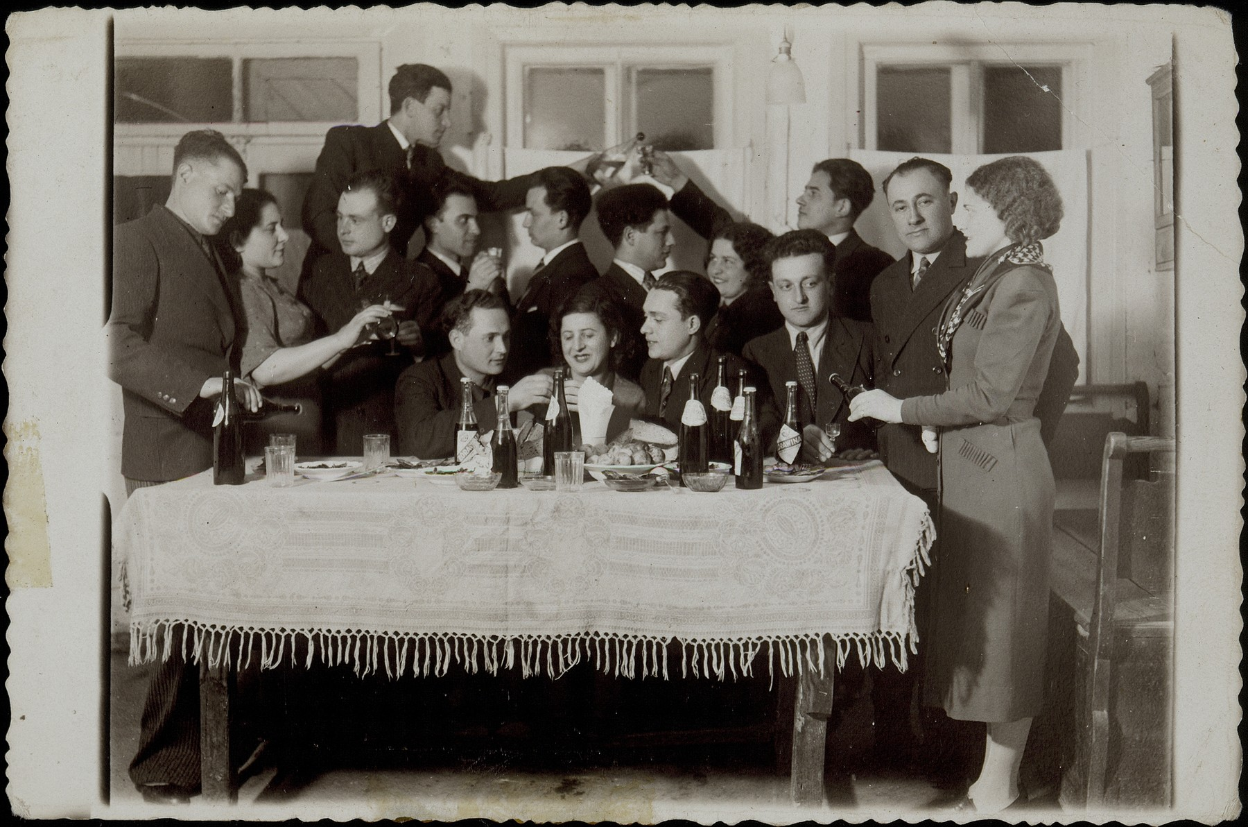 A group of friends enjoy a glass of wine at a Saturday night party.   Standing at the far right is Sarah Michalowski.  Sixth from right (facing left) is Etchke Jurdyczanski (Isaac Juris) and at the far left is Bere Leibke (last name unknown). Names of others are unknown.  Some were members of the Communist party.   Etchke Jurdyczanski (Isaac Juris) survived the Holocaust in Siberia. The majority of the other people in the photo were murdered during the Holocaust.