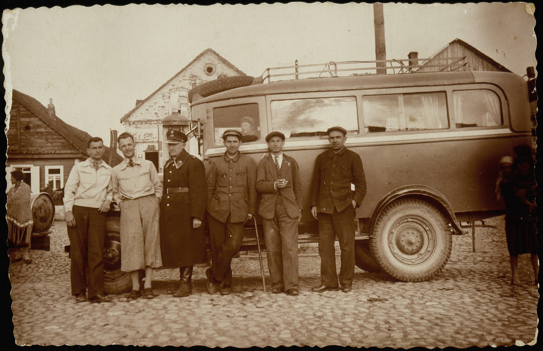 Bus drivers and gas station owners stand next to a bus parked by the shtetl's gas station and bus stop.  (left to right) Moshe Slonimski; Israel Erlich; Avraham Krisilov; a local Polish policemen; and two bus drivers.  Slonimski and Krisilow were co-owners of the Shell Oil station.  Both were murdered by the Germans during the September 1941 mass shooting action.  Israel Erlich was killed by the AK.