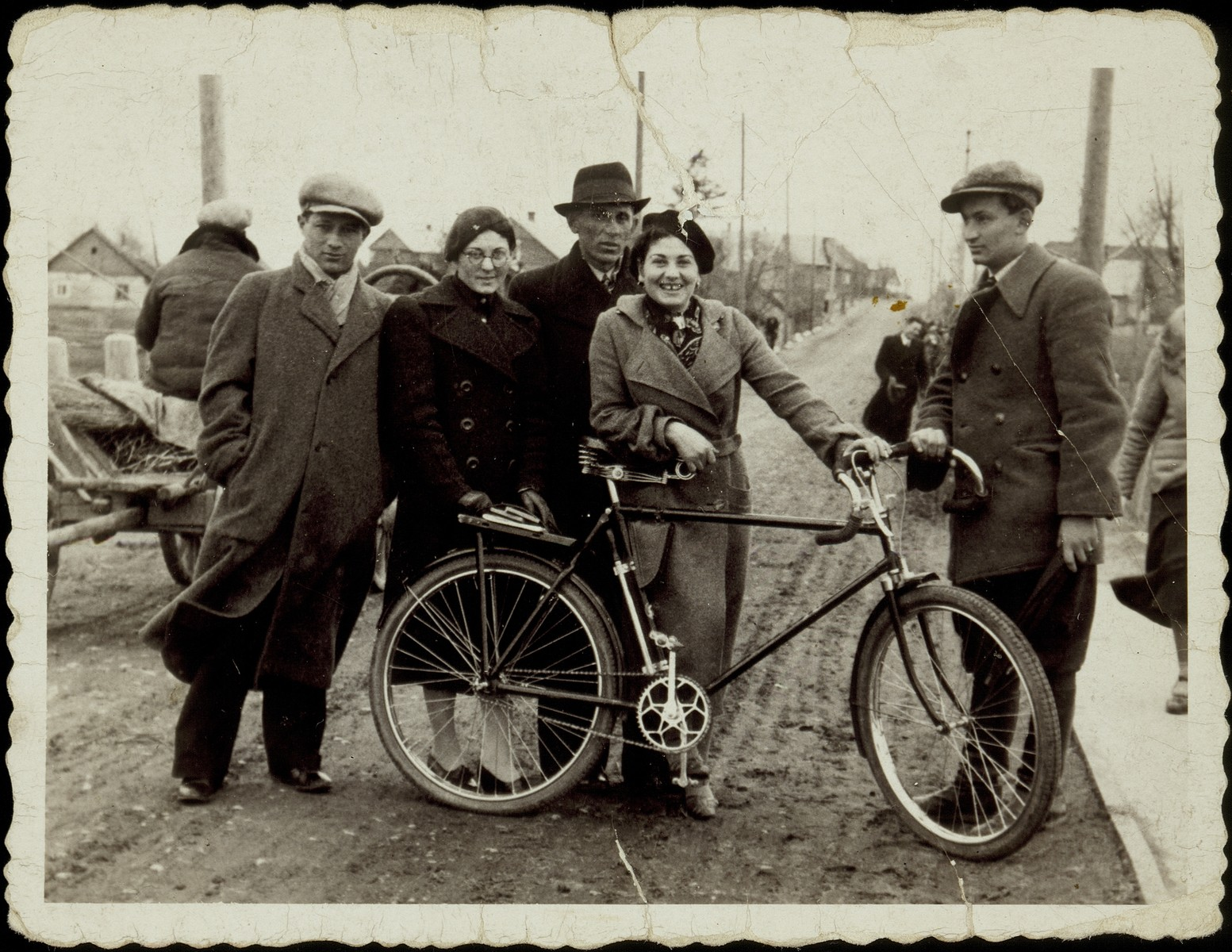 Bluma Lubetski shows off the new bike of her fiance, Etchke Jurdiczansk, on the Vilna Street First Bridge.    From right to left are Etchke Jurdiczanski, Bluma Lubetski, Mickhe Gruznik, Bluma's sister Etele Lubetski, and Hayyim-Yoshke Szczuczynski.    Etele was raped and murdered in Eisiskes during the September 1941 massacre.  The other four survived the war in the Soviet Union.