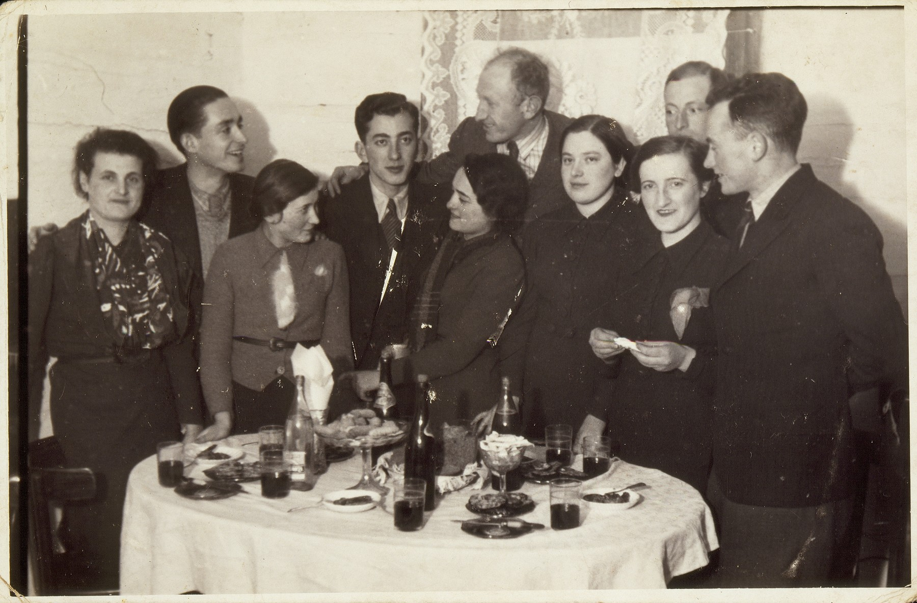 A Saturday night party at the home of Dina Weidenberg.  (right to left)  David Leib Levin; Miriam Kabacznik; her brother Shepske (in the back); Dina Weidenberg, Yehiel Blacharowicz; Kreinele Kanichowski; Dov Wolotzki;  Frumele Abelov, also a successful shopkeeper; an unidentified visitor; and Sarah Lejbowicz, sister of photographer Rephael.   David-Leib survived the war in the forest, and Miriam and Shepske in hiding.  Dov was liberated from Dachau.  Kreinele was killed by members of the AK, including Pietka Barteszewicz, the caretaker of the Polish school where Kreinele once studied. All the others were killed by the Germans during the September 1941 mass shooting action in Eisiskes.