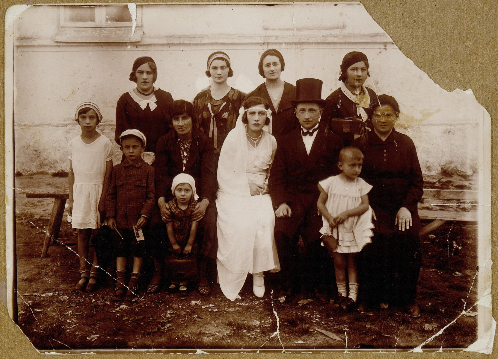 The wedding of Bat-Sheva Rozowski and Rabbi David Zalmanovitz from Ilya.    Bat-Sheva was the daughter of Rabbi Szymen Rozowski.  This was the last wedding celebration in which the entire shtetl participated, as in pre-World War I days.  Sitting next to Bat-Sheva in the shulhoyf is her mother, Rebbetzin Miriam; next to the groom is his mother, Dvorah.  Standing behind them are Bat-Sheva's brother's wife and David's sisters.  In the front row are their little nephews and nieces.  They were all murdered during the Holocaust, the Rozowski family in the September 1941 massacre, Bat-Sheva, David, and their three children in Treblinka.
