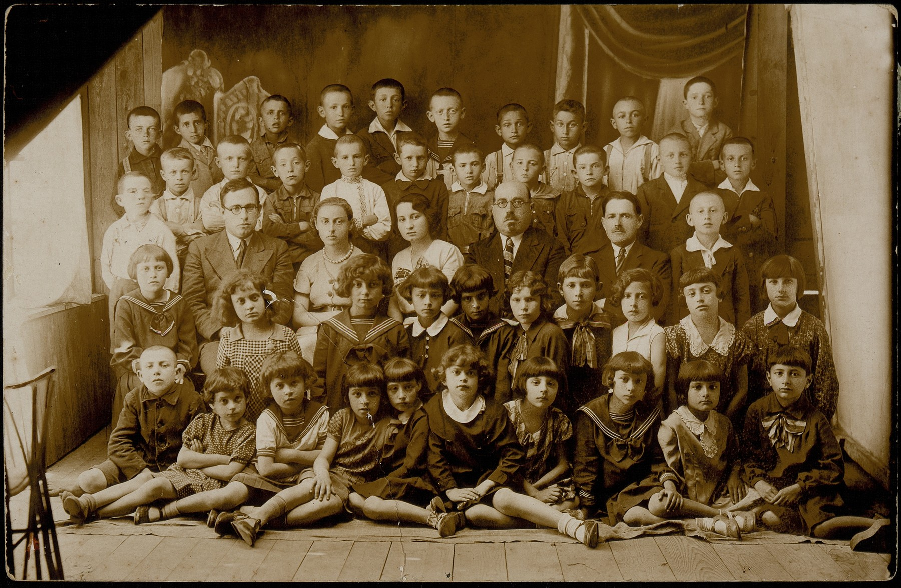 A class picture of the Hebrew school in Eisiskes.  Top row, fifth from right, Moshe Bastunski.  Third row from top, the principal, Moshe Yaakov Botwinik sits in the center.  At the far right is Avigdor Katz.  Second row from bottom, at the far left is Hayya Shlanski.  Sitting on the floor second from right is Hayyala Tawlitski.    Hayya Shlanski emigrated to America with her family.  Principal Botwinik was murdered in the Radun ghetto on May 10, 1942. The identified children were murdered in the September 1941 massacre.