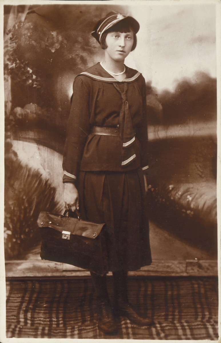 Shoshana Katz, wearing her high school uniform and carrying a brief case, poses for a studio portrait .   Shoshana was the daughter of Alte and Yitzhak Uri Katz, the shtetl's  photographers and pharmacists. She was killed by the Germans during the September 1941 mass shooting action in Eisiskes.
