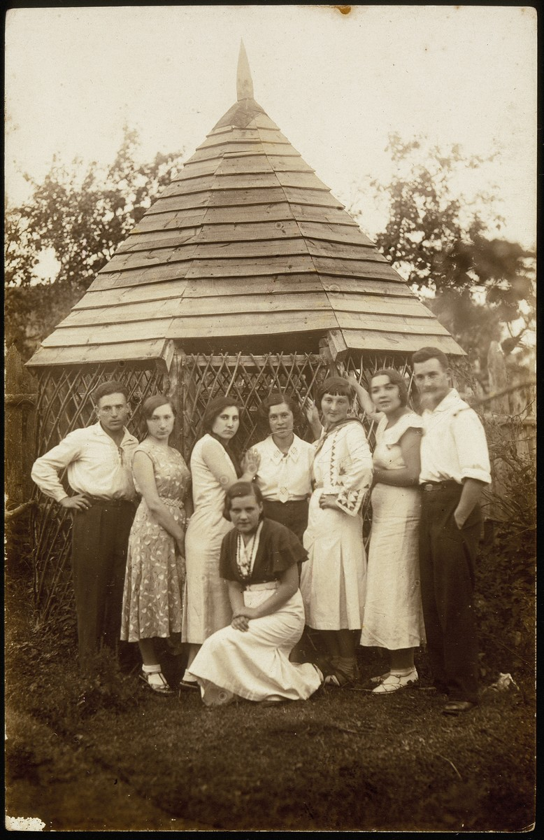 Members of a Zionist group pose in front of a wooden gazebo in the Kabacznik garden.    From right to left: Hanan Polaczek, Malka Zahavi Matikanski, Esther (Etele) Katz Resnik, Haike Bielicki, a guest, Szeine Blacharowicz and her (first) husband Motke Burstein.  Seated in the front: Malka Nochomowicz.  Hanan Polaczek and Malka Zahavi Matikanski immigrated to Palestine.  Esther (Etele) Katz Resnik immigrated to Colombia, South America.  Szeine Blacharowicz survived the Holocaust in hiding.  All others were murdered either in the September 1941 massacre or in other locations.