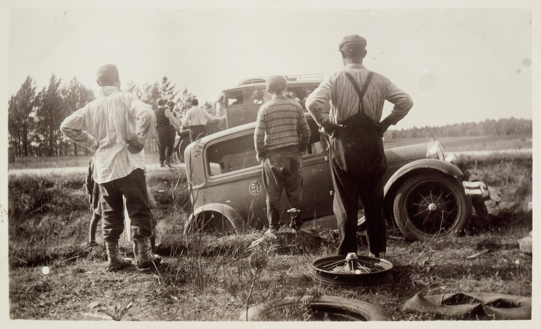 People look on with dismay at an automobile that ended up in a ditch after receiving a flat tire.