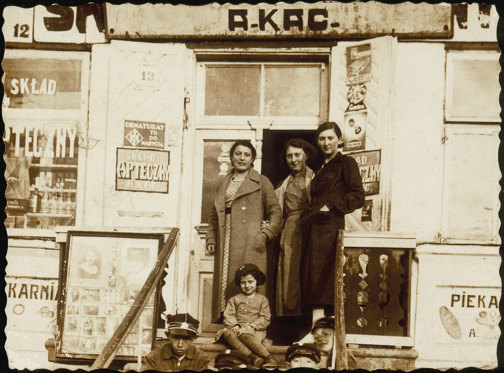 A group of friends stands on the steps of Alte Katz's pharmacy.   (right to left) Esther (Etele) Katz, her sister Shoshana, and their friend Fania Botwiniki.  Seated on the steps (right to left): Avigdor Katz, his nephew Yitzhak Sonenson, Yitzhak's cousin Gittele Sonenson, and two friends.  To the right of the steps is the entrance to the bakery  below street level.  On the left is a display of photos from the Katz photography studio.    Only Esther and Yitzhak survived the war.