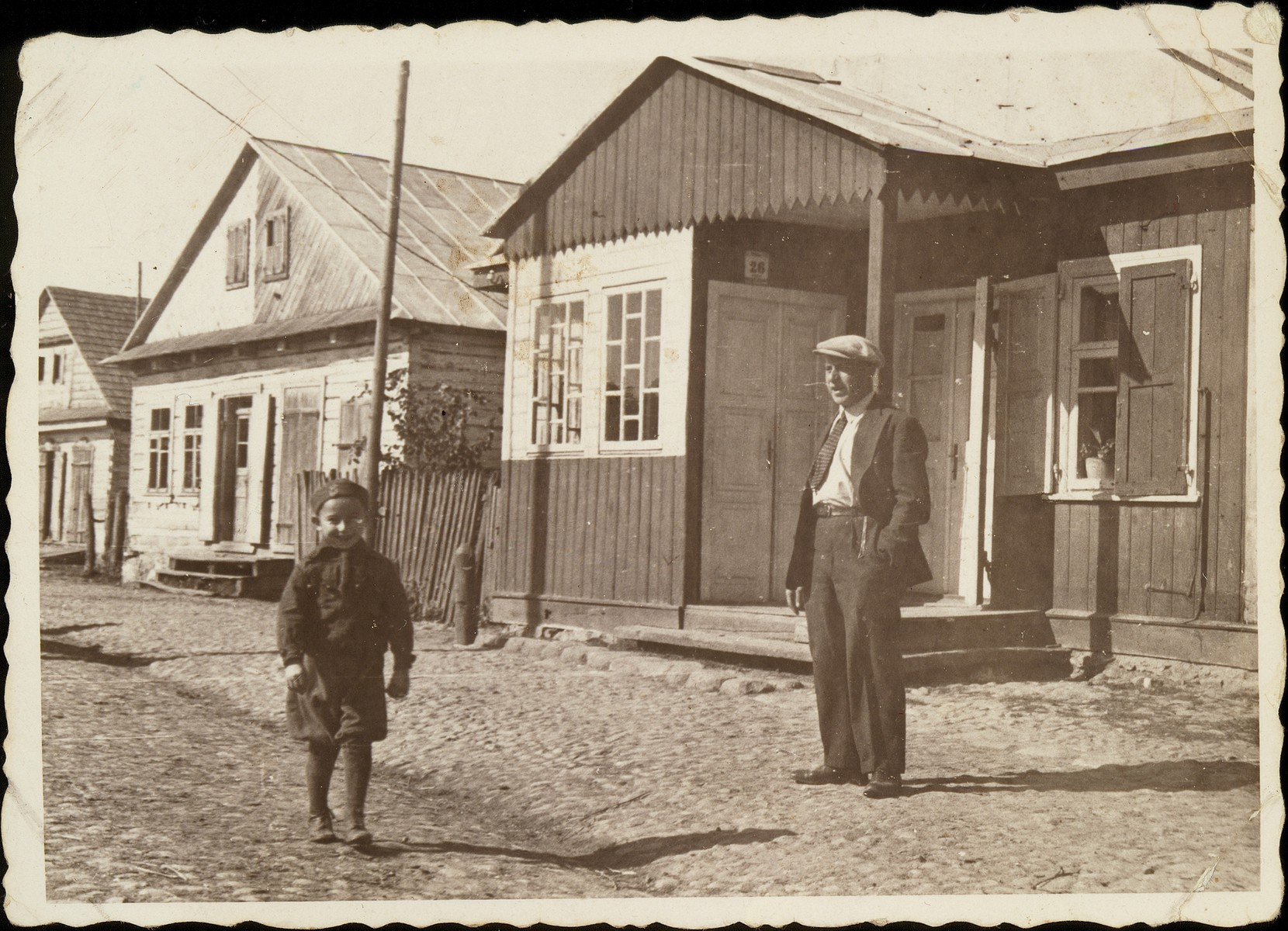 A father watches his son walk to school down a street of the shtetl.