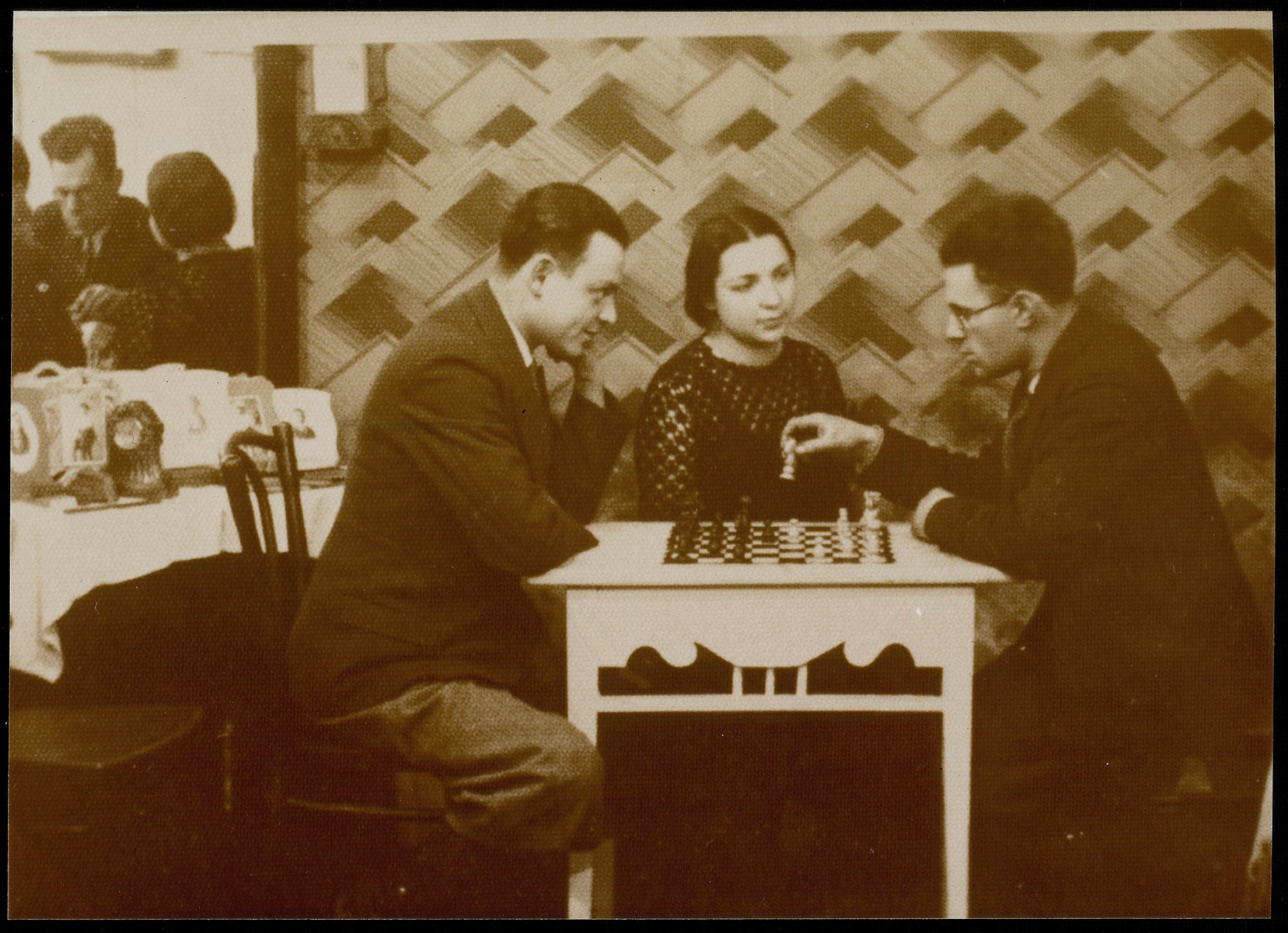 Two men play chess while Malka Matikanski looks on.  Malka Matikanski sitting in the center and Velvke Kaganowicz is on the right.  The man on the left is unidentified.  The photograph was taken in the photographer's house on Vilna Street.  Malka Matikanski  immigrated to Palestine.  Velvke Kaganowicz, his wife and children were murdered by the Germans during the September 1941 killing action in Eisiskes.