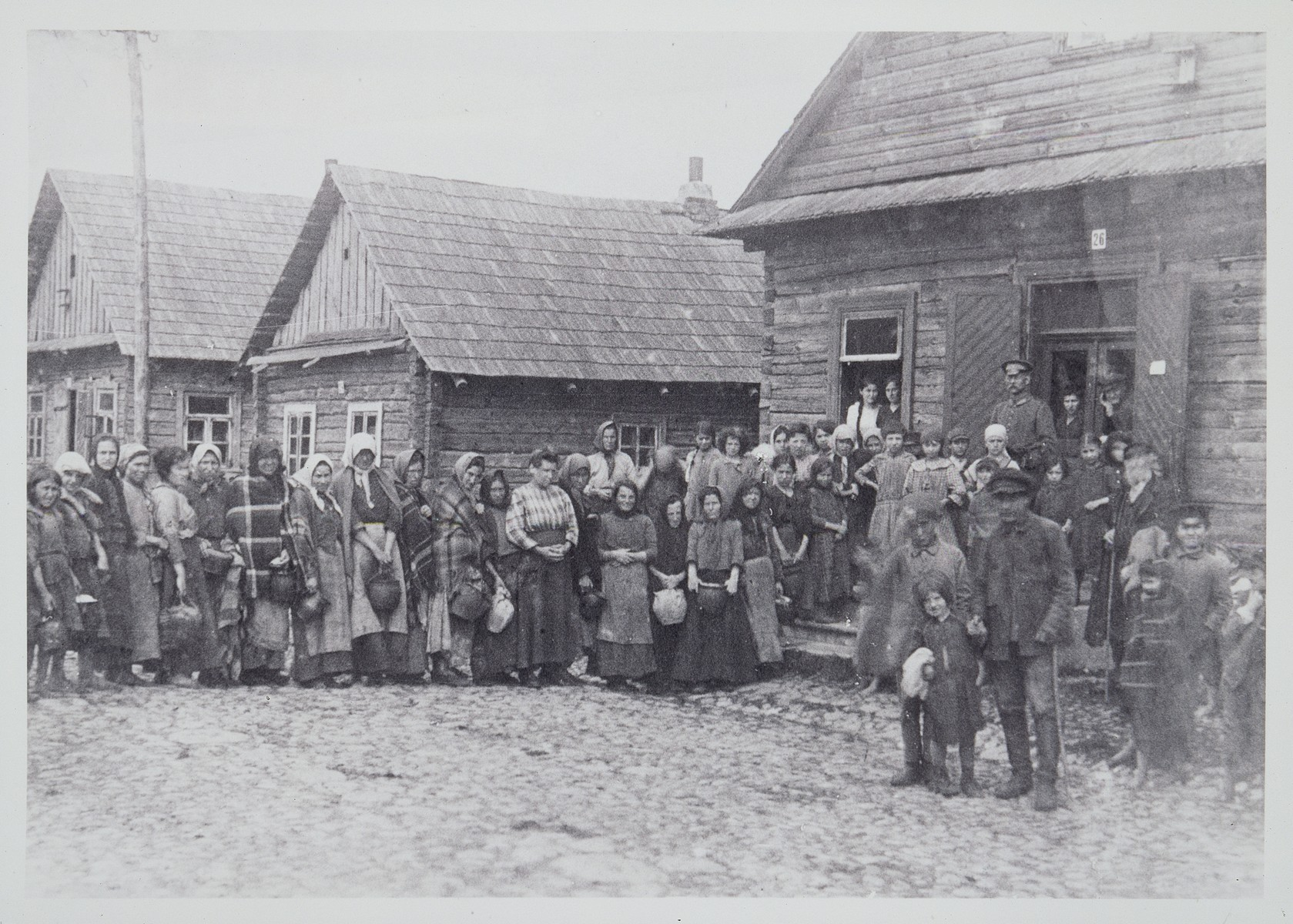 Jews and non-Jews await food distribution in front of the soup kitchen.   German soldiers helped to distribute the food.  The building that housed the soup kitchen belonged to Leib der Grober (the fat one), who immigrated to the United States. The middle house belonged to Avraham-Asher, and the third house to Hayyim Leibke Paikowski.