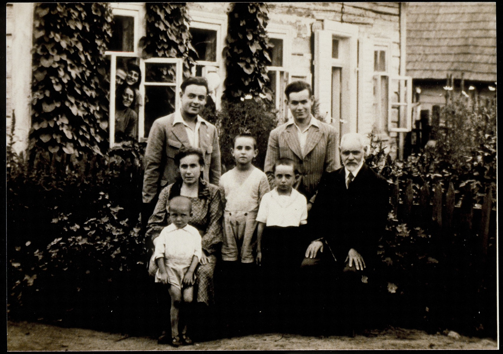The Matikanski family poses for a family portrait in the garden outside its home.   Pictured are Reb Dovid Matikanski, his wife Nehama (nee Pecker) and two of their younger sons, Haikl (standing left) and Yitzhak.    Dovid Matikanski was one of Eisikes's custom tailors.   He, the three young children with him and the people peering out the window were murdred in the September 1941 mass killing action.  Nehama, Haikl and Yitzhak perished in Majdanek.