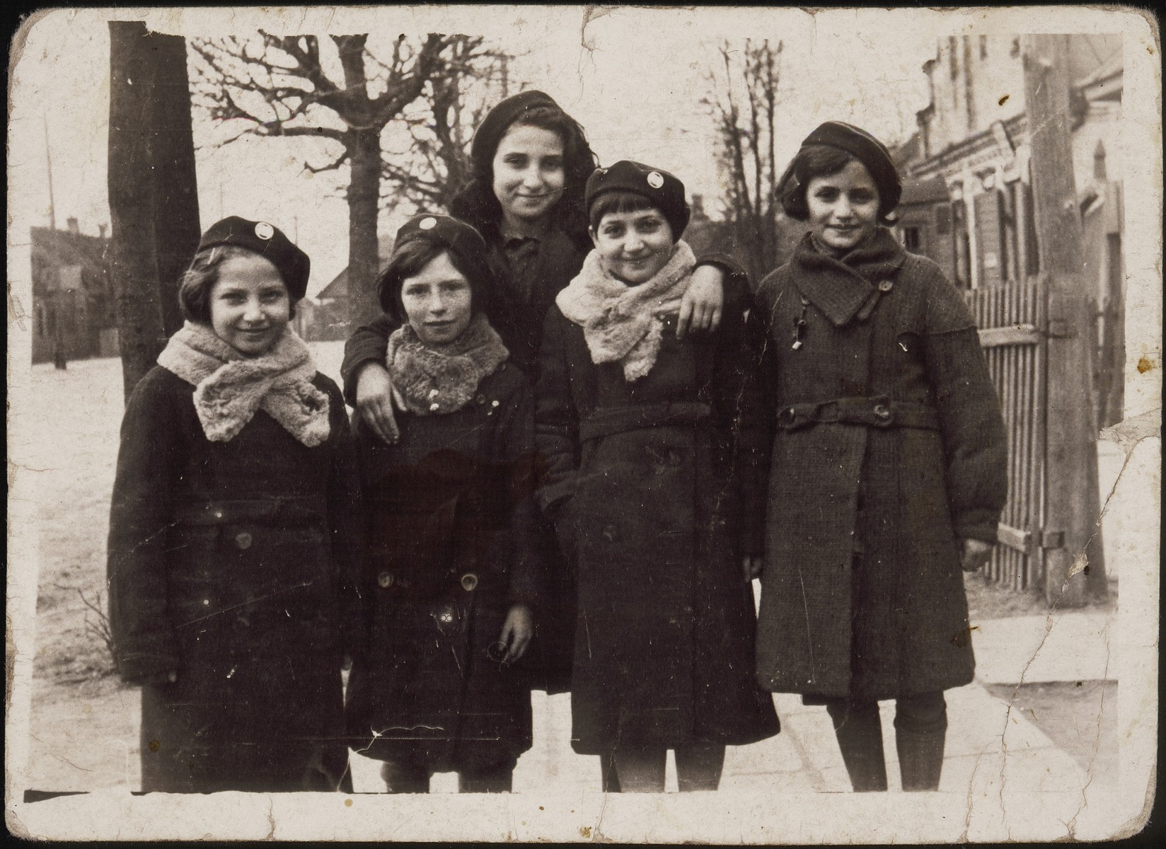 Five school girls wearing winter coats stand together on a street in Eisiskes.