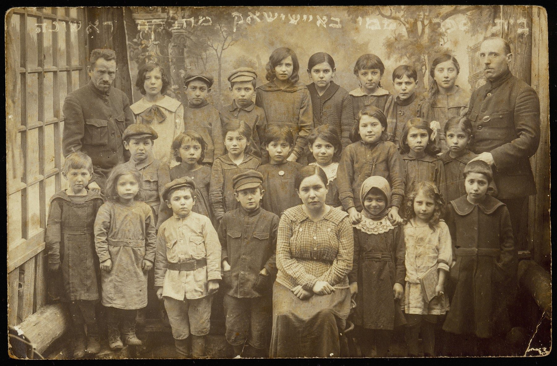 The first grade class photo of  the first coeductional Hebrew day school in Eisiskes.    The three Hebrew teachers are Moshe Yaakov Botwinik (right), Yaakov Schneider (left) and Rivka Rubinstein (sitting in the first row). The students: (first row, right to left) (first name unknown) Rosenblum, name unknown, Luba Ginunski, Shaike Segal, Shaul Schneider, (first name unknown) Slepak and Esther Katz ; (second row, right to left) Titinski, Paikowski, (first names unknown); fourth girl is a Ginunski; (third row, right to left) (first name unknown) Moszczenik, Taibke Kosowski, Lube Senitski, Dov Wilenski, and Miriam Lanski.
