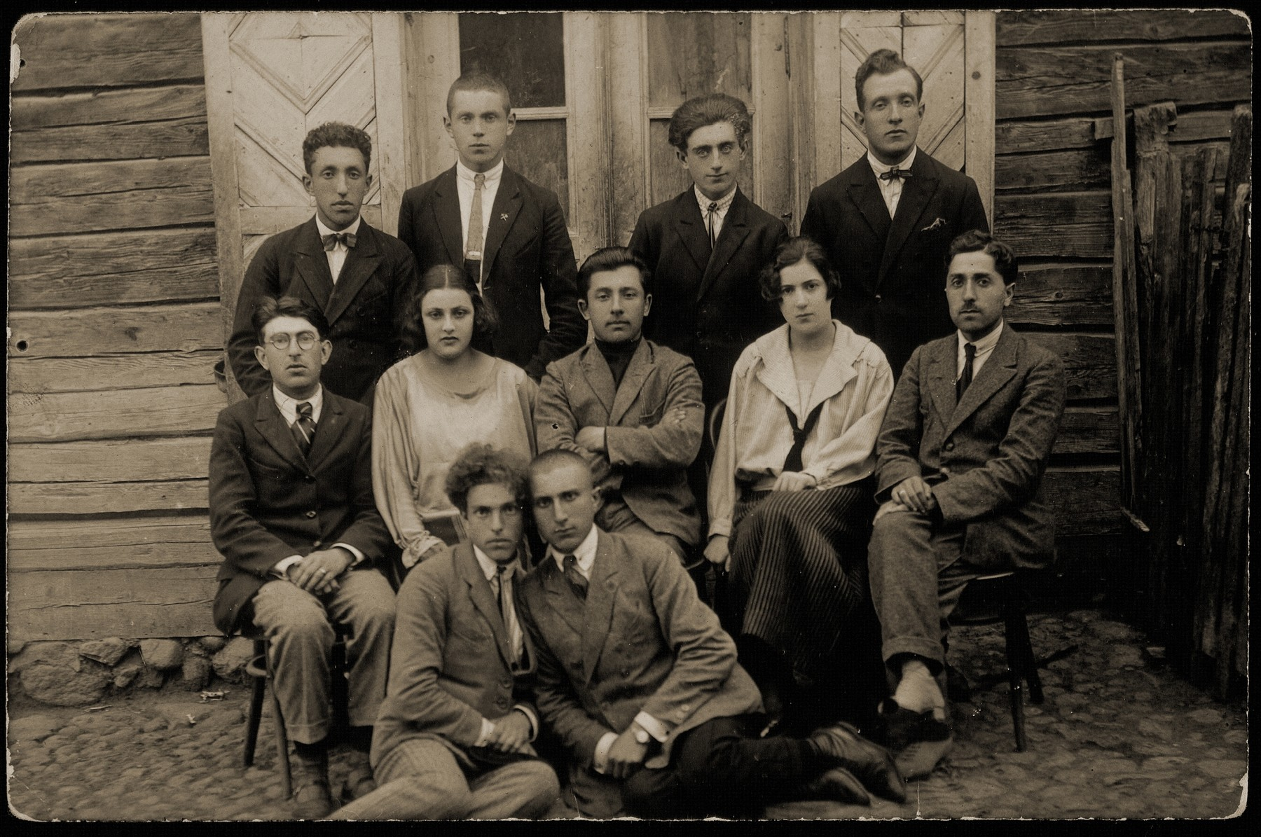 A group of friends poses in front of a wooden house.    Standing at the extreme left is Shlomo Kiuchefski.  Sitting at the extreme left is Avraham Rozowski, son of Rabbi Szymen Rozowski.  His brother Uri Rozowski is sitting on the ground on the left.  Others are unknown.    Shlomo Kiuchefski was murdered by the AK.  Avraham Rozowski and his family were murdered by the Germans during the September 1941 killing action in Eisiskes.   Uri Rozowski immigrated to Palestine.
