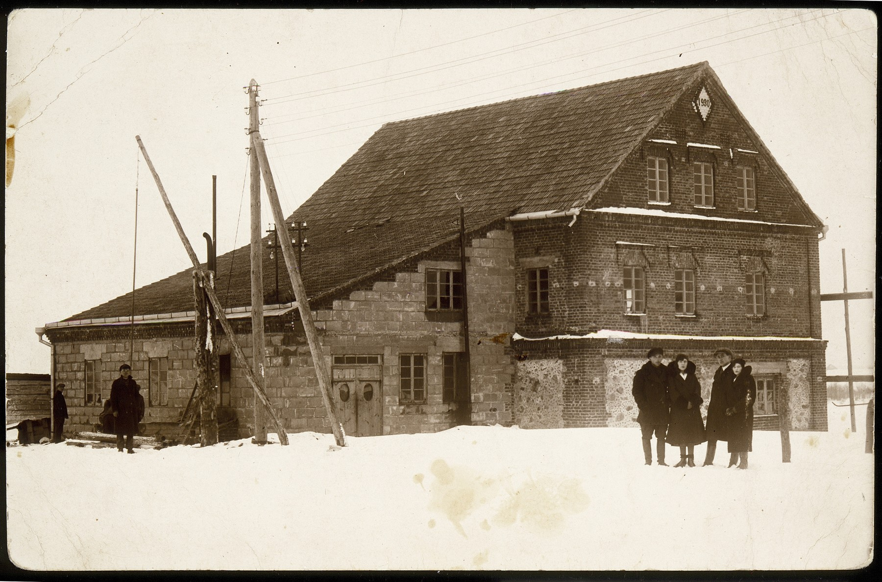 The inauguration of an electrical power plant building, which also housed the new electric flour and saw mills.  The power plant was built and owned by the Kiuchefski family and Moshe Kaganowicz.  Standing in front of the building are (left to right) Shlomo Kiuchefski, Dora Zlotnik Berkowicz, Zeev Kaganowicz, and wife, Masha (née Kiuchefski).    Two Kaganowicz brothers, Moshe and Zeev married two Kiuchefski sisters, Hannah and Masha.  Moshe and Hannah moved to Vilna.  In addition to his partnership in the electric power plant, Moshe also served as an agent for a cosmetic company.  Dora immigrated to Palestine; Zeev and Masha were murdered by the Germans; Shlomo was killed by the AK.