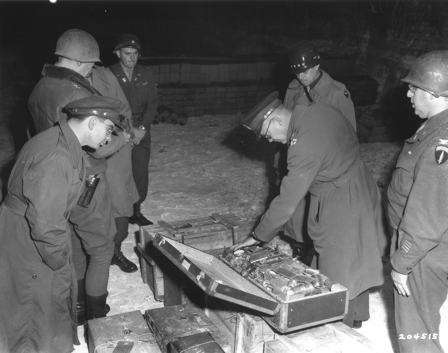 General Dwight D. Eisenhower, Supreme Allied Commander in the West, General Omar Bradley, and General George S. Patton examine a suitcase containing silverware looted by the Nazis that was hidden in the Merkers salt mine.