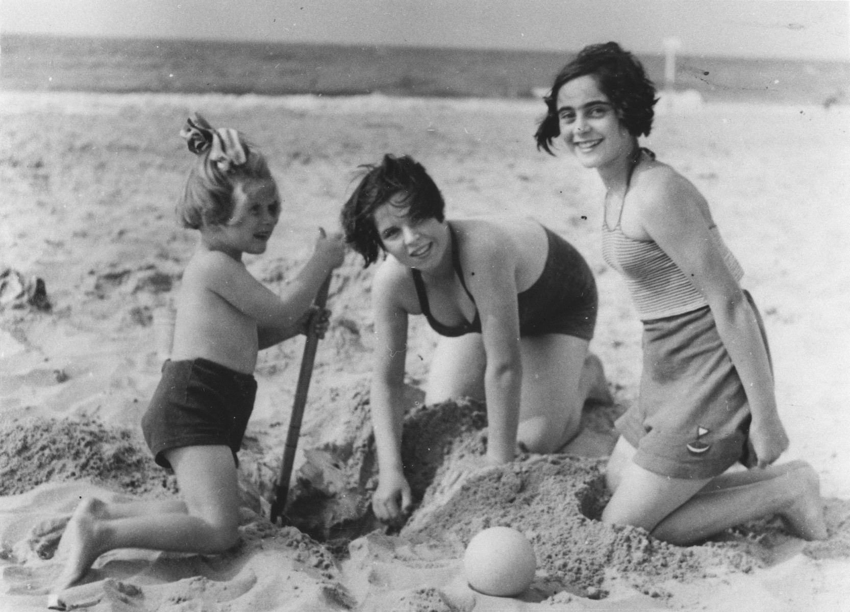 Doris Bloch and her cousin Annelise Hollander play in the sand at the beach.