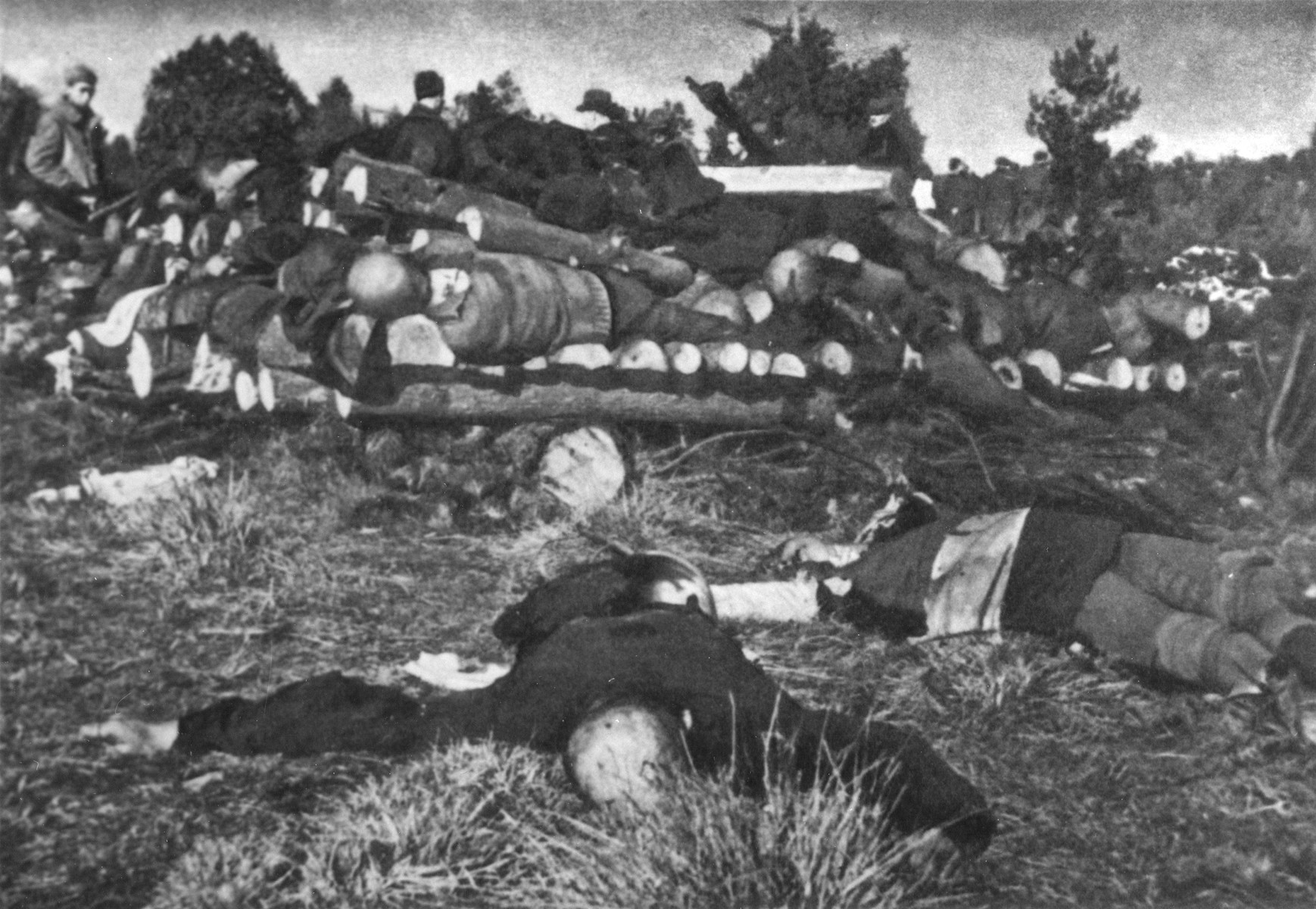 Corpses in Klooga stacked for burning.    Soviet investigators can be seen in the background.