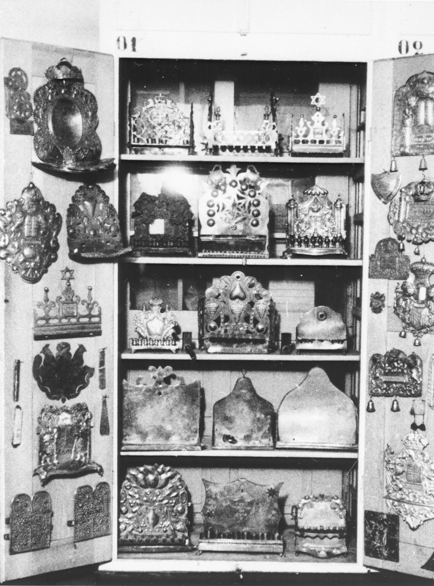 Display of silver Hanukkah menorahs and Torah breast plates confiscated by the Nazis.