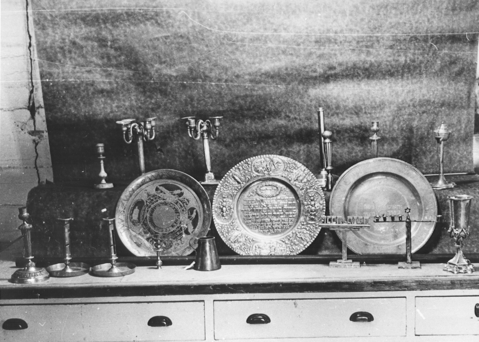 Display of silver Hannukah menorahs, Sabbath candlesticks and seder plates confiscated by the Nazis.