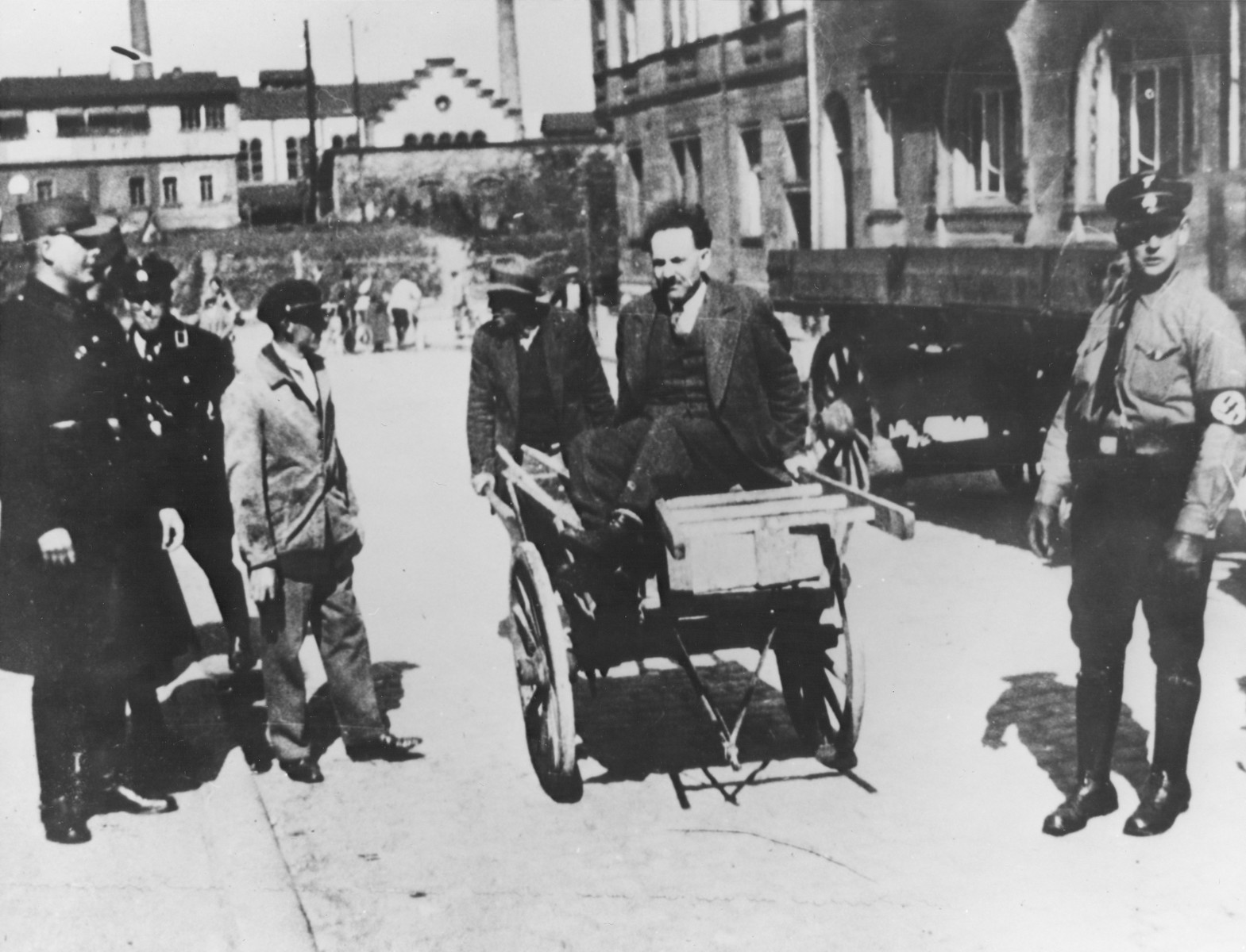 SS men publicly humiliate an unidentified man by wheeling him  through the streets in a cart filled with dirt from street cleaning.
