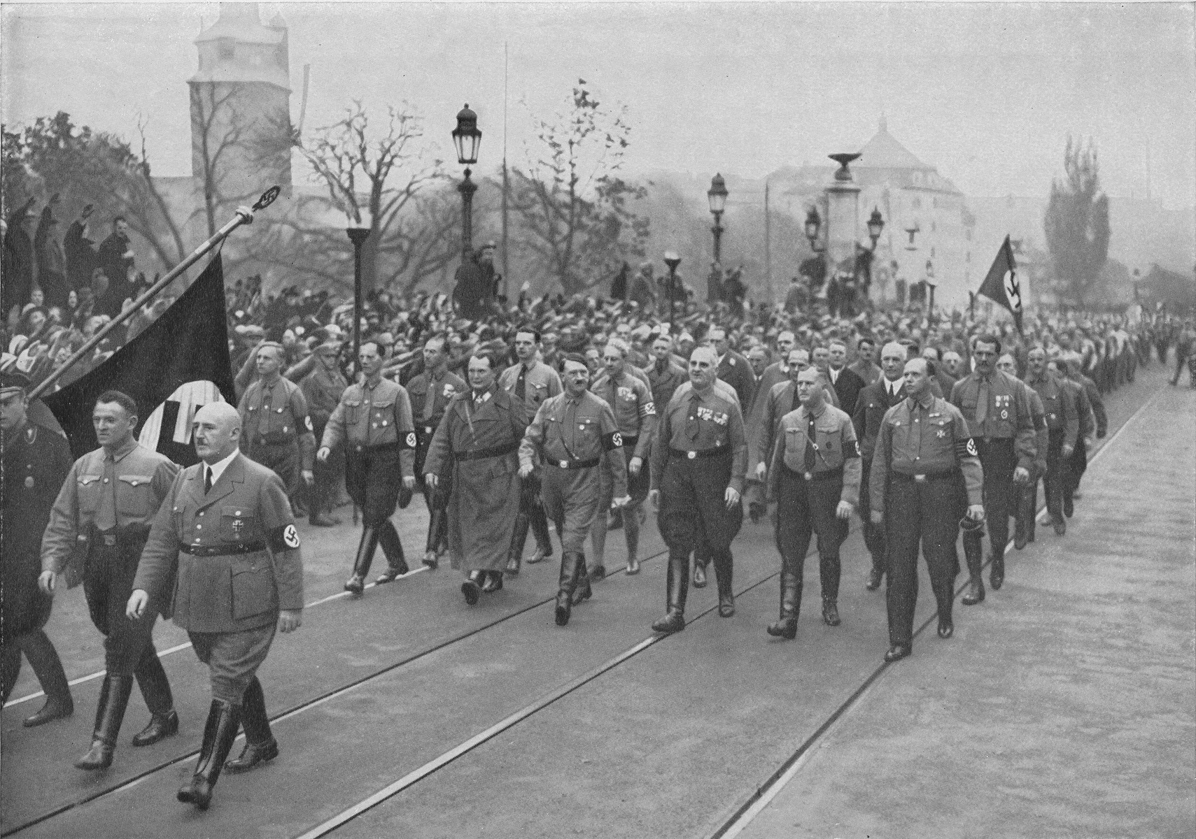 Adolf Hitler (center, front row) and Hermann Goering (third from left, front row) lead a march through the streets of Munich to commemorate the November 8-9, 1923 Beer Hall Putsch. Julius Streicher marches with the Nazi colors (lower left corner, third from left).