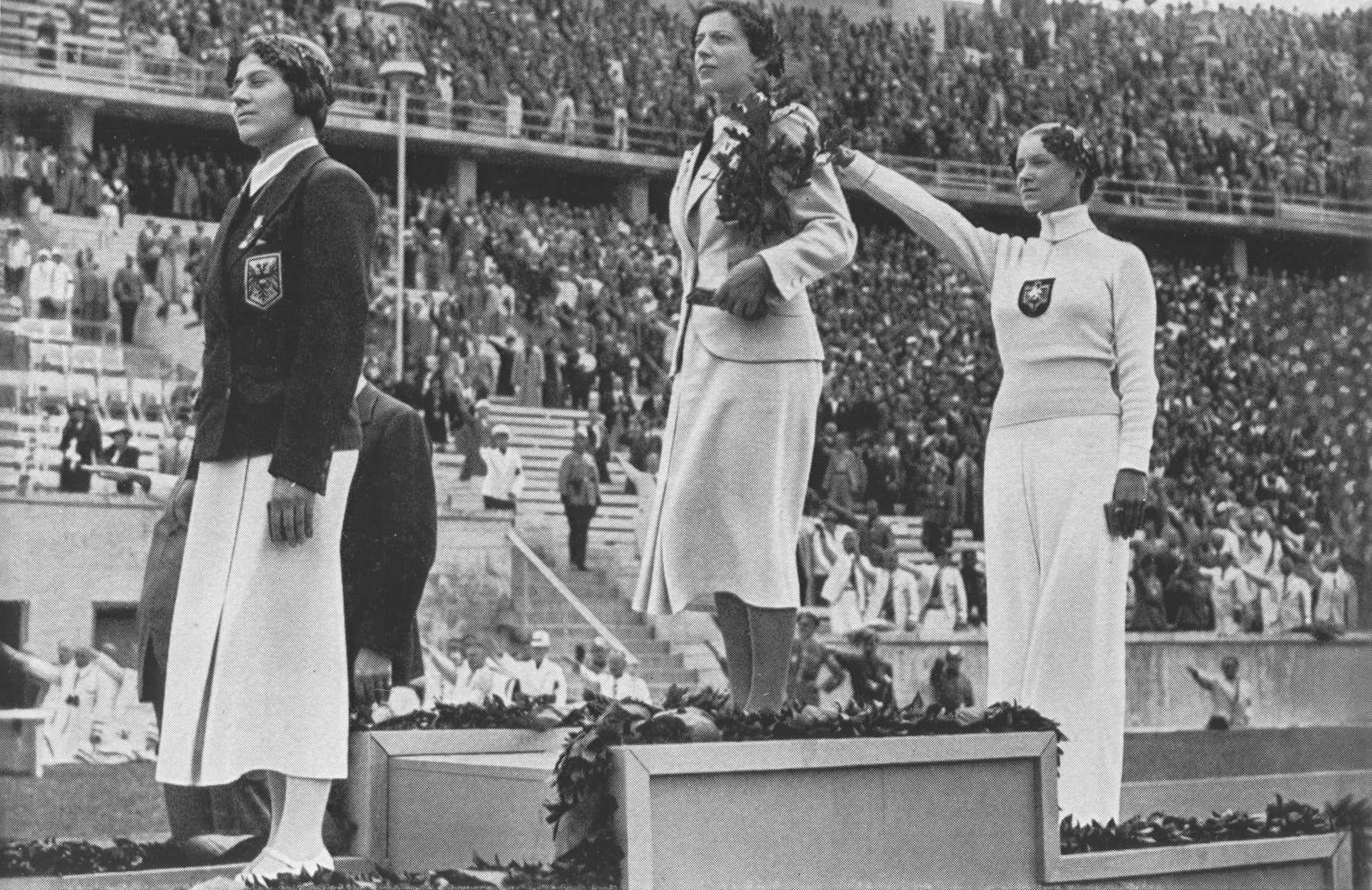 The awarding of medals for fencing at the 1936 Berlin Olympic games.   The Gold medalist was Ilona Schacherer of Hungary, the Silver medalist Helene Mayer of Germany, and the Bronze medalist Ellen Preis of Austria.  Mayer, a championship fencer, was a half-Jewish German  residing in the United States and was allowed to join the German team only after American diplomatic pressure.