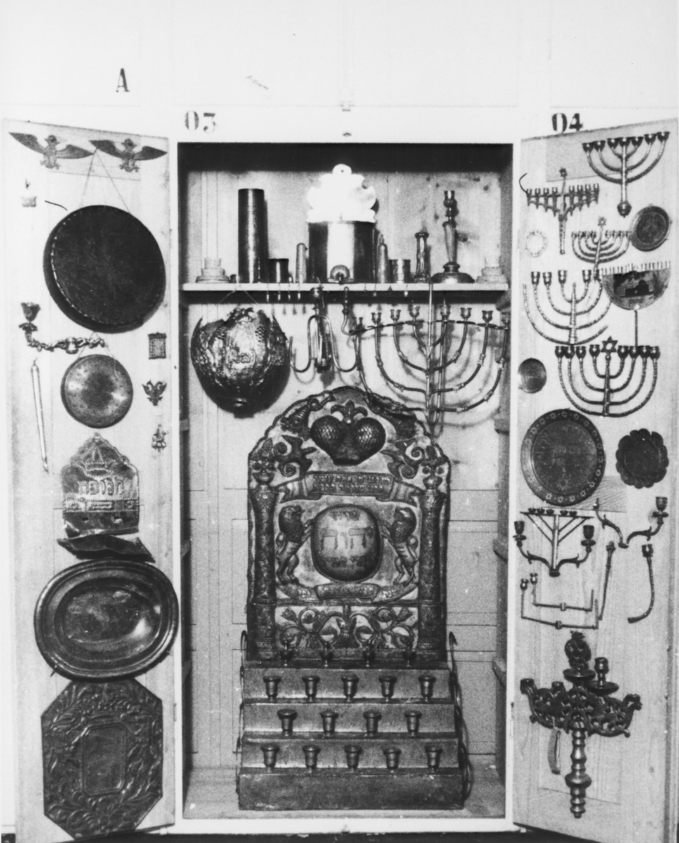 Display of damaged silver Hanukkah menorahs and other ritual objects confiscated by the Nazis.