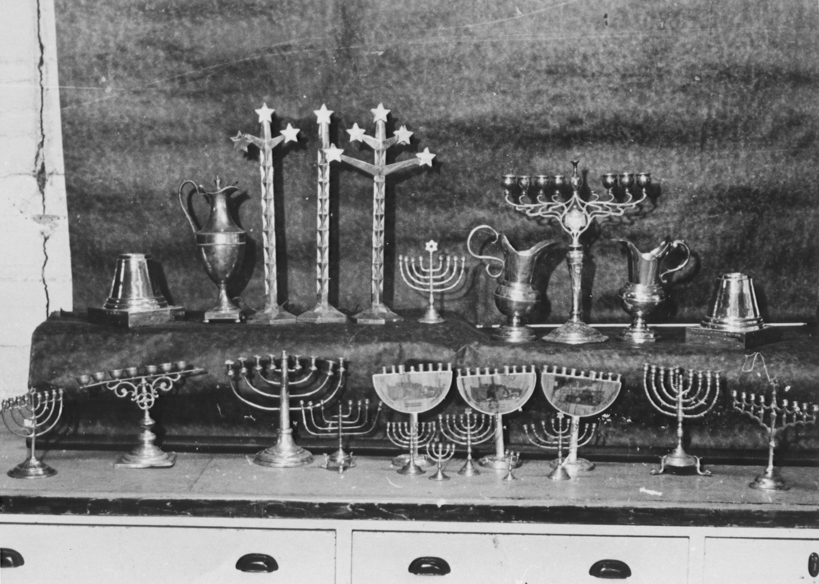 Display of silver Hanukkah menorahs and other ritual articles confiscated by the Nazis.