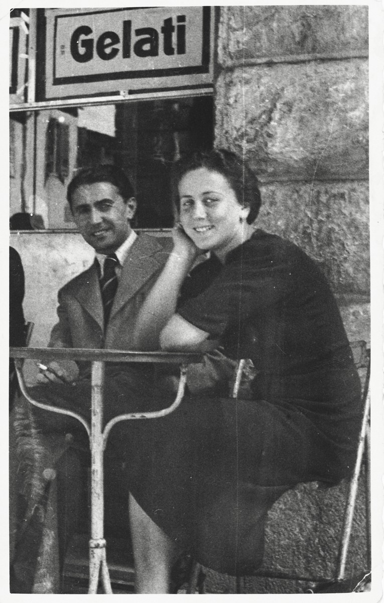A young Jewish couple from Poland sits outside an ice cream parlor in Pisa, Italy.  Pictured are Henryk and Chaja (Ringelheim) Rosenfeld.