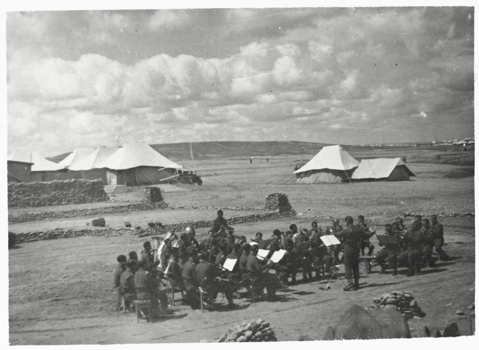 Members of the orchestra of the 2nd Polish Corps (Anders Army) perform outside at their military base in the Iraqi desert, where they were stationed from the summer of 1942 until the summer of 1943.