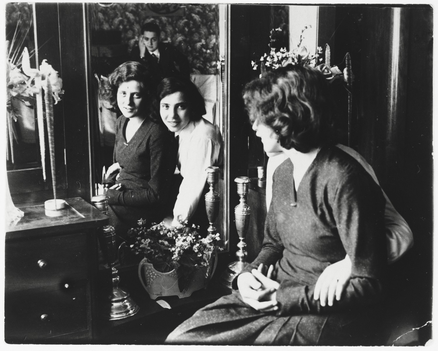 Two Jewish friends look at themselves in a mirror.  Among those pictured is Chaja Ringelheim (left).