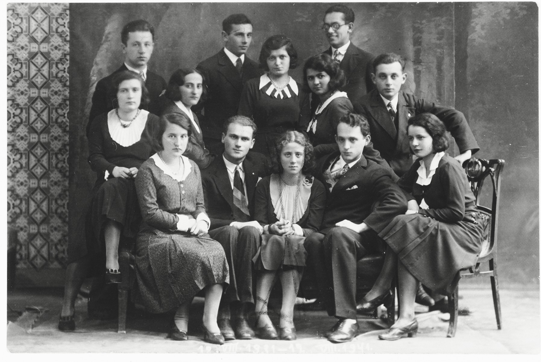 Studio portrait of a group of young adult Jewish friends.  Among those pictured is Chaja Ringelheim (front row, center).
